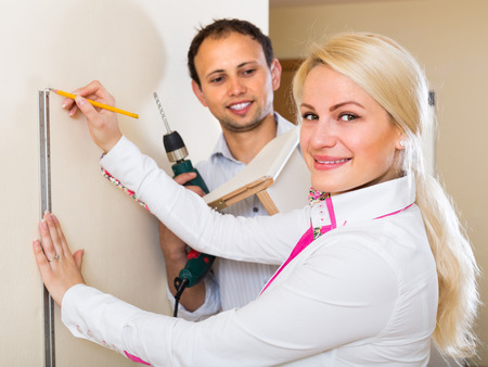 repairs: Positive smiling young couple  makes repairs together at home Stock Photo