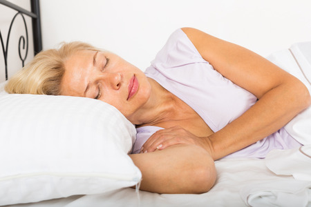 dream: Blonde middle-aged woman sleeping on white pillow in bed at home