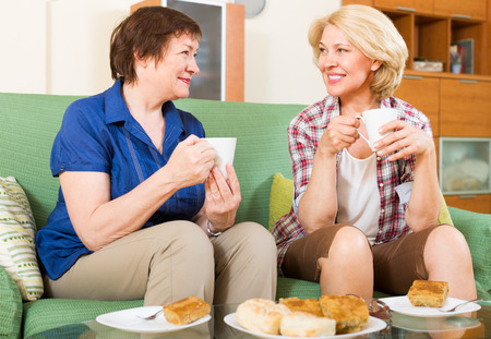 talkative: Two elderly women sitting at the table with tea and gossiping in home interior