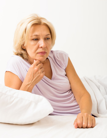 ennui: Upset mature woman laying in bed with dropped eyes