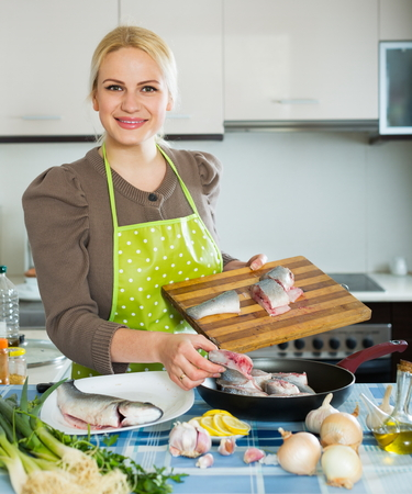 Blond girl with raw fish at home kitchen