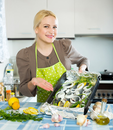 fryingpan: Cheerful blonde woman cooking fish  in frying pan at home kitchen