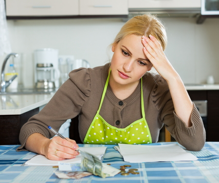 parsimony: Casual housewife filling in utility payments bills at  home