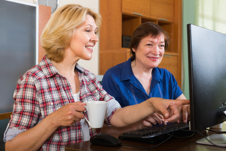 mature women: Two mature women sitting in front of PC with coffee and laughing