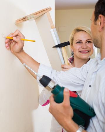modifying: young smiling couple hangs bookshelf on a wall