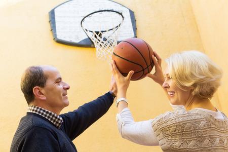 spouses: Positive senior spouses throwing the ball into basket Stock Photo