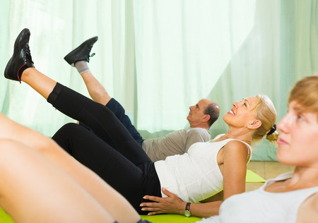 to incline: Female trainer showing happy mature couple how to incline the body