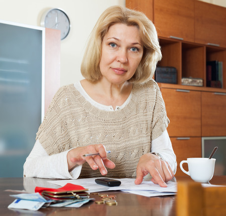 wistful: Wistful mature woman thinking about the financial issue at  home Stock Photo