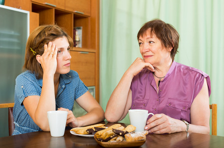 pensioner: Woman pensioner having conversation with her daughter during coffee