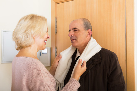 corrects: Mature european wife corrects scarf on positive belowed husband at the doorstep