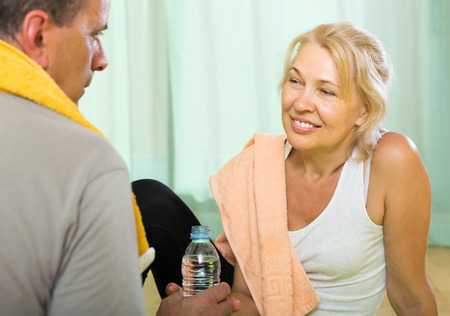 spouses: Positive smiling senior spouses smiling after training indoor