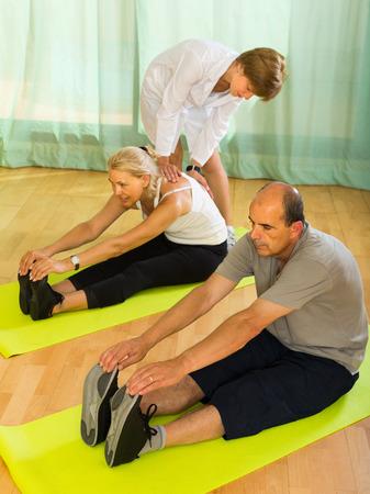 personal medico: El personal m�dico ayudar a los c�nyuges de edad avanzada en el gimnasio. Centrarse en el hombre Foto de archivo