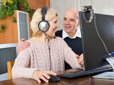 skype: Positive wife and her husband are sitting at the computer and  talking on Skype with european friends indoor