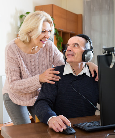 global retirement: Happy senior spouses using PC for video calls at home and smiling