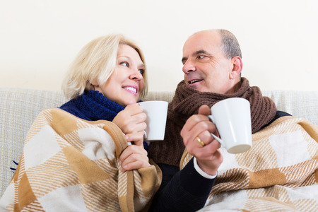 Mature spouses under blanket drinking tea on couch