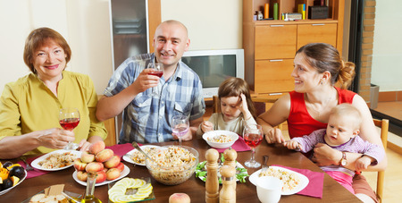 three generations: happy three generations family drinking and eating  at home Stock Photo
