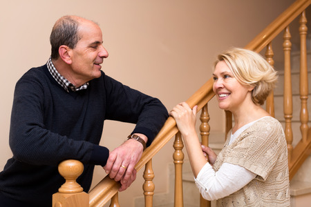 stairs: Mature  couple posing near wooden stairs indoors at home. Focus on man