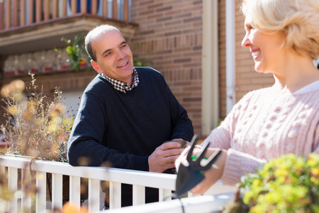 balcon: Mature female talking with smiling male neighbor at balcon