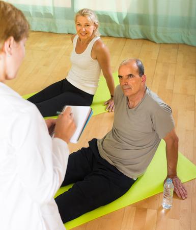 studio happy overall: Medical staff watching yoga class for elderly indoor Stock Photo