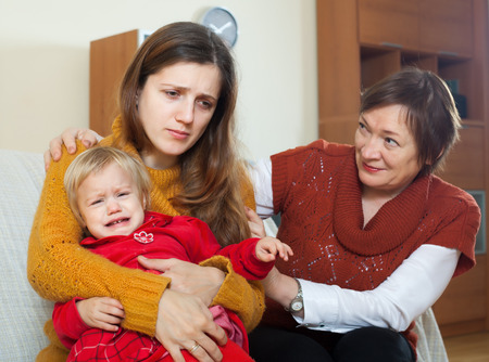 fracas: Young mother has trouble. Mature woman comforting adult daughter with baby