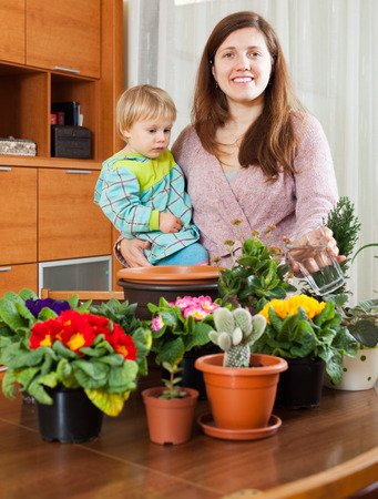 replant: Happy smiling young mother with baby transplanting potted flowers at table in home Stock Photo