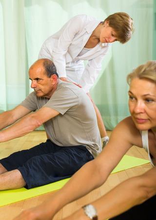 personal medico: El personal m�dico en el gimnasio de ayudar a los c�nyuges ancianos para tomar posici�n correcta. Centrarse en el hombre