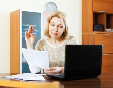 ruminate: serious mature woman with laptop and documents at table in office Stock Photo