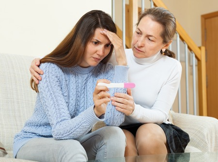 home pregnancy test: Mature woman  consoling the sad teen daughter with pregnancy test at home