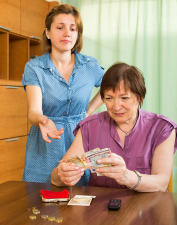 strife: Young girl and her aged mother having conflict about financial problems