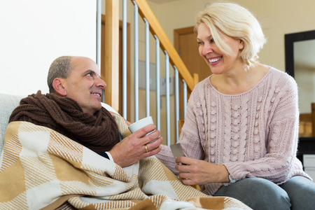 sick leave: Mature wife gives hot tea and medicine to husband on sick leave at home Stock Photo