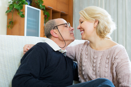 spouses: Portrait of happy elderly spouses sitting on sofa indoor Stock Photo