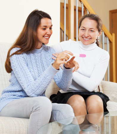 home pregnancy test: Happy mature woman and her daughter with pregnancy test at home interior