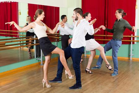 merry dancers: Tree happy european couples dancing rock-and-roll in dancing-class