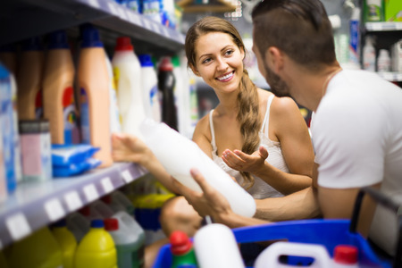 vend: Young russian  people choose some detergents in the shop
