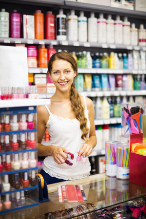 desk clerk: Smiling store clerk with nail polish at cash desk Stock Photo
