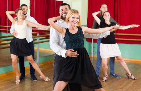baile moderno: Grupo de adultos j�venes felices tienen clase de tango en el estudio de baile. Enfoque selectivo