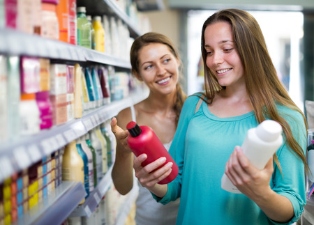 vend: Adult beautiful woman in good spirits selecting shampoo at the store