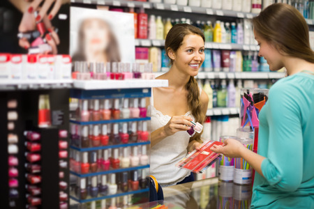Young girl choosing new nail polish color at store