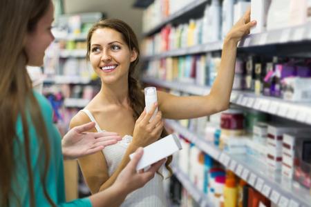Feliz muchacha rusa comprar crema cosmética en el centro comercial