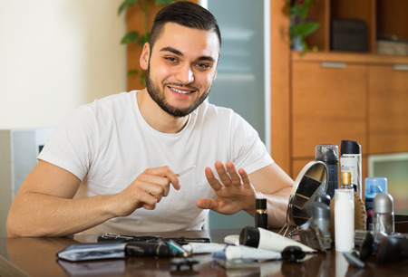 metrosexual: Handsome smiling metrosexual guy doing manicure at home