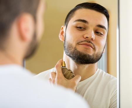 perfume: portrait smiling man applying perfume for keeping fresh