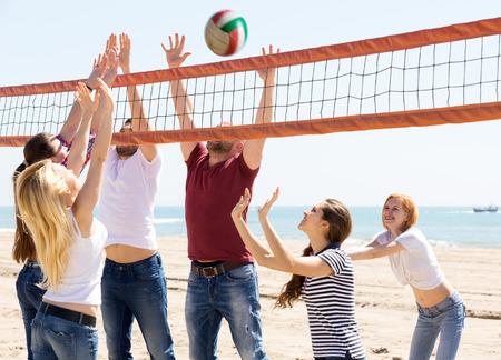 voleibol: feliz grupo de amigos que se divierten en la playa y jugando a la pelota