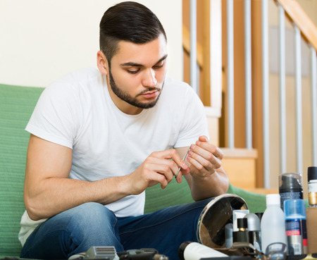 25s: Positive young handsome guy doing manicure at home Stock Photo
