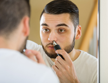 electric trimmer: Guy remove hair from his nose and ears with trimmer Stock Photo