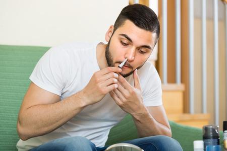 nariz: chico joven que usa el condensador de ajuste para eliminar el vello de la nariz en el hogar