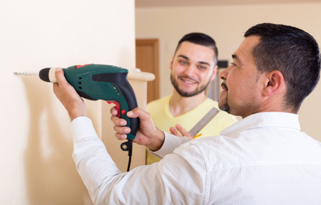 work from home: Two skilled men doing maintenance work at home