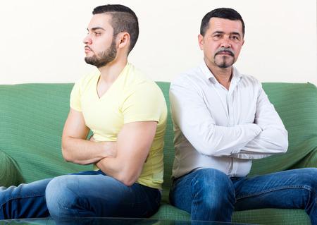 hombres gays: Disputa doméstica entre el padre y el hijo adulto en el sofá de la sala de estar