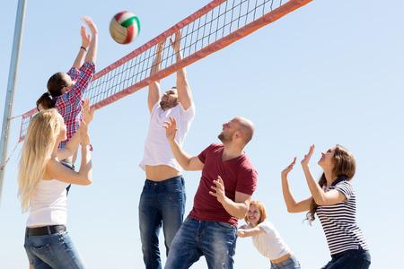 pelota de voleibol: Adultos felices que lanzan peligro en red y riendo. Conc�ntrese en el par