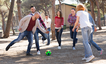 Positive adults friends chasing ball outdoors at sunny day Stock Photo