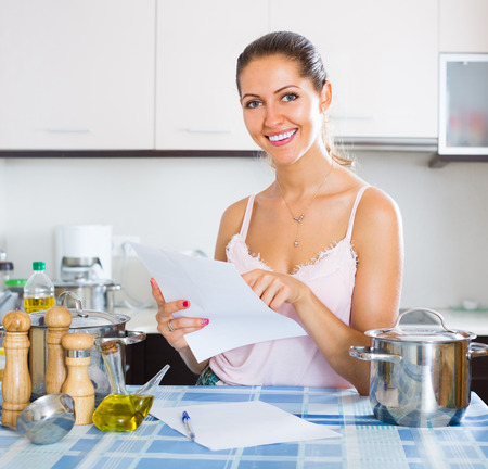 advantaged: Young woman signing documents at the kitchen and smiling